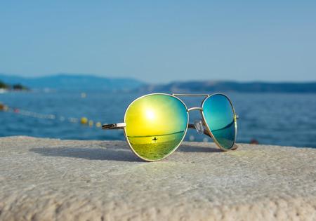Zonnebril met overzeese bezinning over het strand Stockfoto