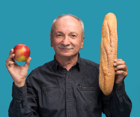 Senior man with apple and baguette on a blue background photo