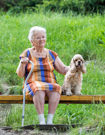 aging american: Old woman and her dog sitting on a park bench Stock Photo