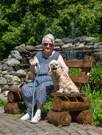 Old woman sitting on a bench with a dog  at summer park