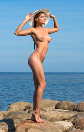 nude pose: Beautiful nude woman posing on stones at the beach Stock Photo