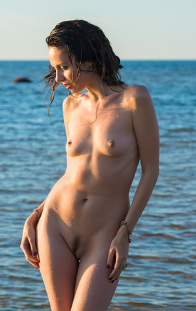 Beautiful naked woman an the beach against the sea