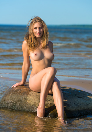 hat nude: Beautiful nude woman posing on stones at the beach Stock Photo
