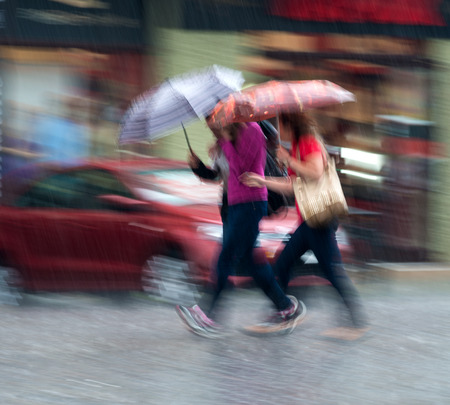 windy city: People walking down the street on a rainy day in motion blur