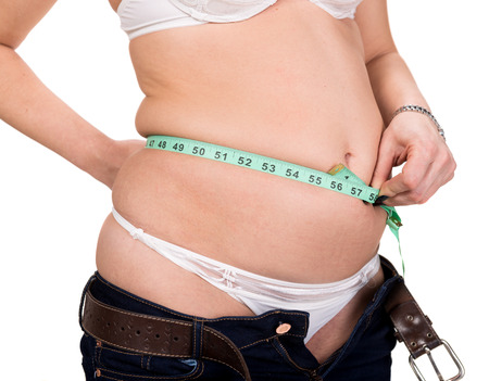 Overweight woman measuring waistline on a white background  photo
