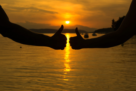 Man and woman showing thumbs up on the beach at sunset