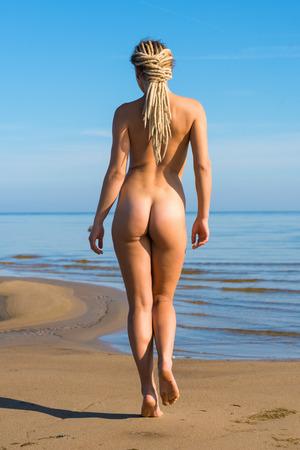 Красивая голая женщина позирует на пляже