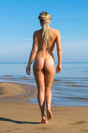mujer desnuda: Hermosa mujer desnuda posando en la playa Foto de archivo