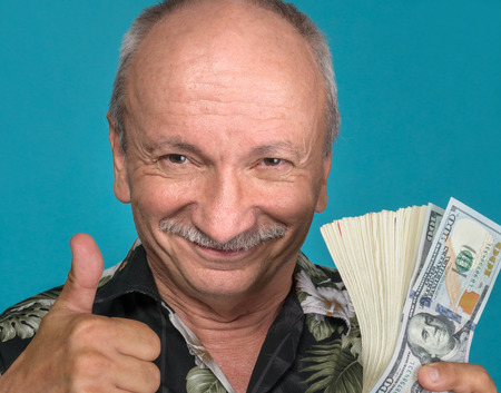 Lucky old man holding dollar bills on a blue background photo