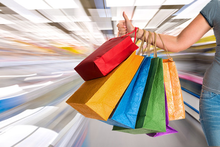 Woman holding shopping bags and gesturing thumb up at shopping mall 免版税图像