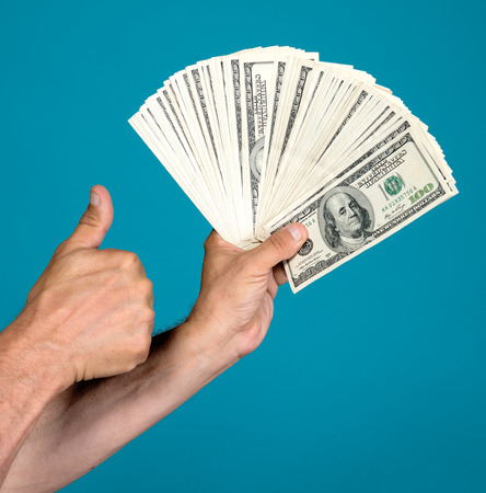 Man holding dollar bills and gesturing thumb up on a blue background photo