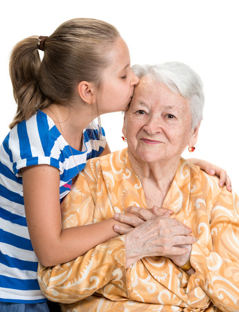 grandmother: Granddaughter kissing her old grandmother on white background