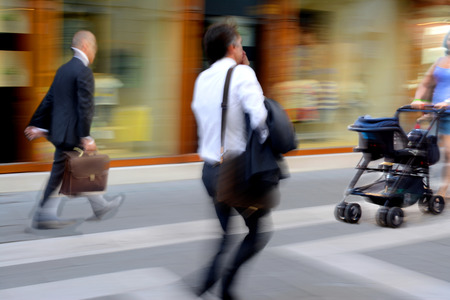 Business people and woman with stroller in the street. Intentional motion blur photo