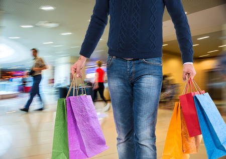 Man with shopping bags at shopping mall photo