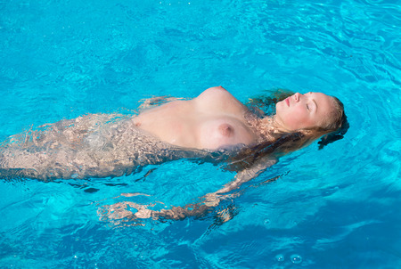 Beautiful young naked woman enjoying summertime in swimming pool