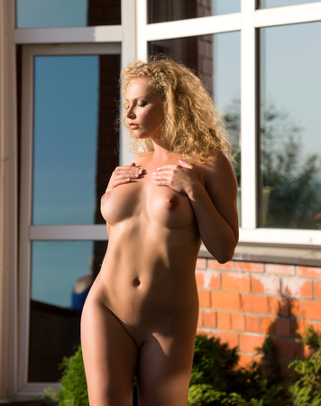 Beautiful young nude woman enjoying summertime