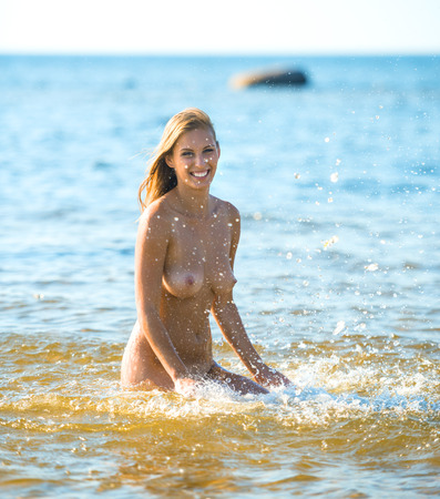 Beautiful young naked woman enjoying summertime on the beach 免版税图像
