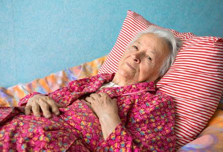 Senior zieke vrouw liggend op bed liggen op bed Stockfoto