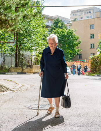 Old woman walking with a cane down the street of the city photo