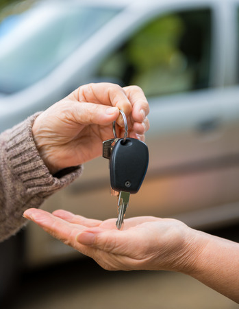 Woman giving car keys to another woman photo