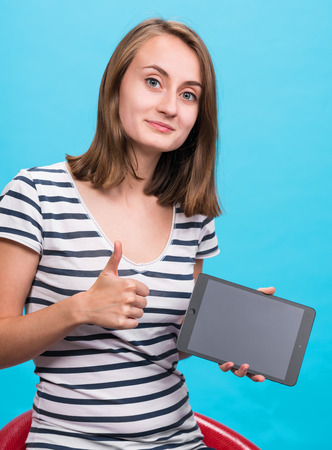 Smiling girl with tablet pc computer on blue background photo