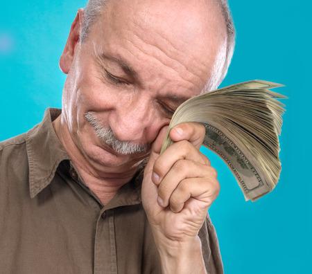 Lucky elderly man holding dollar bills on a blue background photo