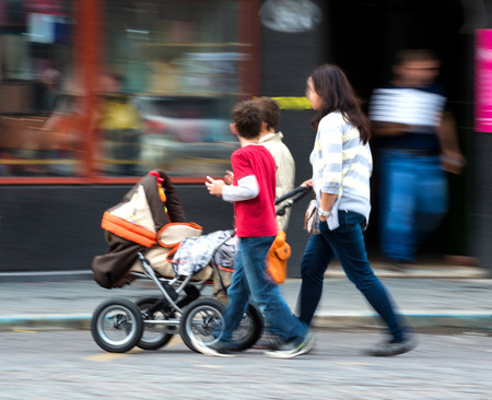 Mother with toddler child in stroller and children in motion blur