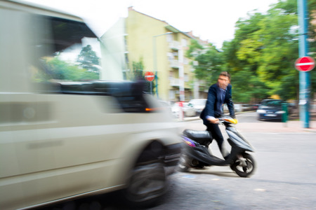 Dangerous city traffic situation with a motorcyclist and a bus in motion blur