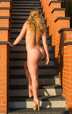 nude woman posing: Young beautiful naked woman on the stairs in the evening sun posing in the evening sun