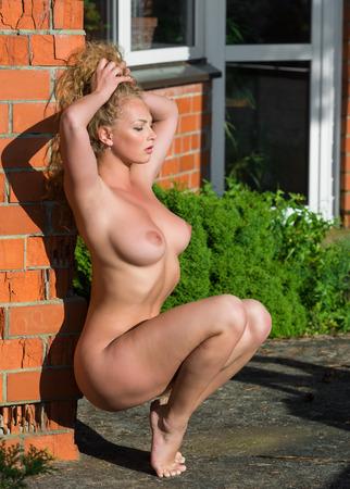 Красивая молодая голая женщина позирует возле кирпичной стены