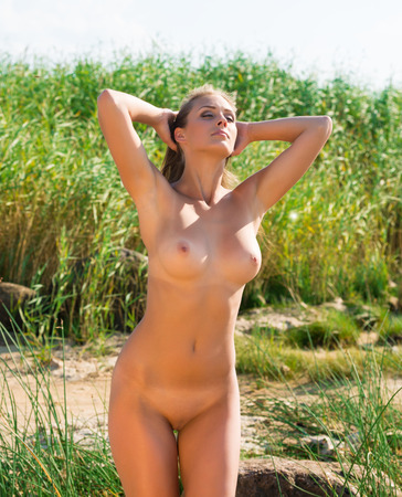 adult nudity: Beautiful young nude woman posing on nature background