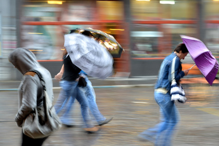 People walking down the street on rainy day. Intentional motion blur