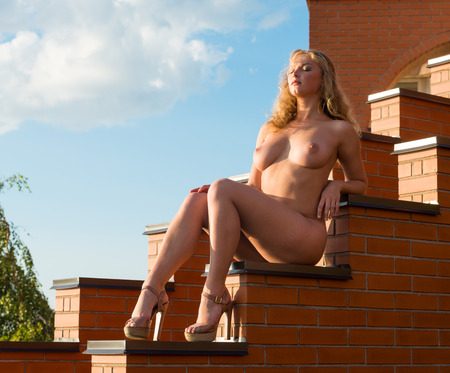 topless women: Young beautiful naked woman posing on the stairs in the evening sun