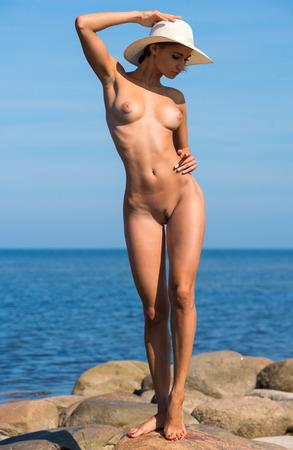 nue plage: Belle jeune femme nue dans le chapeau blanc posant sur des pierres sur la plage Banque d'images