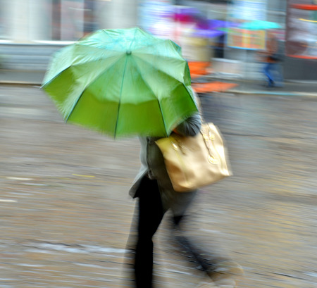 Woman walking down the street on a rainy day in motion blur