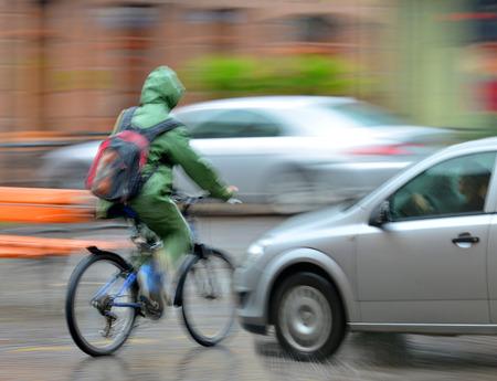 ciclista: Situaci�n peligrosa tr�fico de la ciudad con el ciclista y el coche en la ciudad en el desenfoque de movimiento