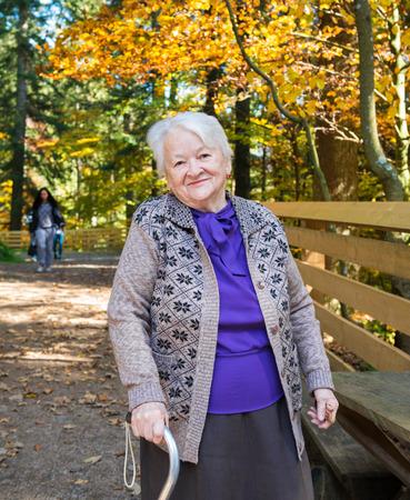 Portret van oude glimlachende vrouw in de herfst park Stockfoto