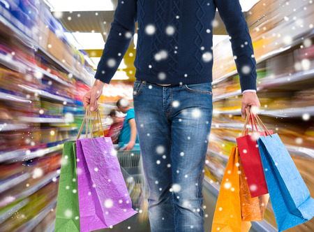 Man with shopping bags at shopping mall.  Christmas and holidays concept