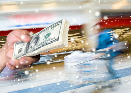 Man holding stack of dollar bills at shopping mall.  Christmas and holidays concept photo