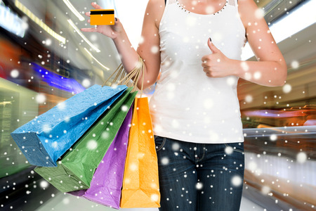 Woman holding shopping bags and credit card at shopping mall.  Christmas and holidays concept photo