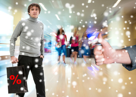 Man with shopping bag, another man gesturing thumb up at shopping mall photo