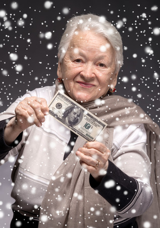 woman holding money: Smiling old woman holding money in hands