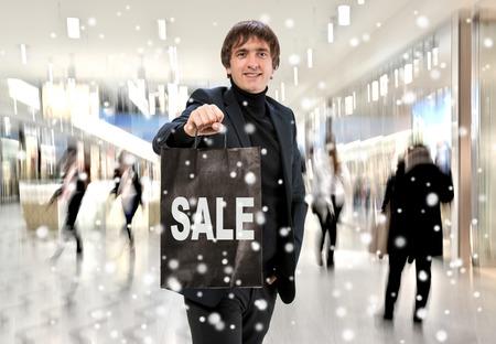 Smiling man n with shopping bag at shopping mall photo