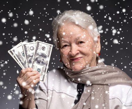 woman holding money: Smiling old woman holding money in hands. Christmas and holidays concept Stock Photo
