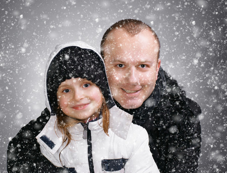 outwear: Smiling father and daughter in winter outwear.  Christmas and holidays concept