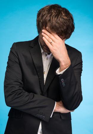 miserable: Portrait of unhappy businessman on a blue background