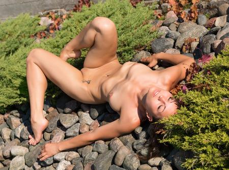 nudity girl: Beautiful young nude woman posing  on stones.
