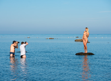 Fotografen und Aktmodell am Strand. Fotosessions am Strand