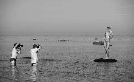 Fotógrafos y modelo de desnudos en la playa. Sesión de fotos en la playa Foto de archivo - 34073317