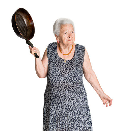 Angry old woman with a pan on a white background Фото со стока